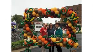 3 people pose inside a frame made of a variety of balloons at the Fairfax Fall Festival 2016.