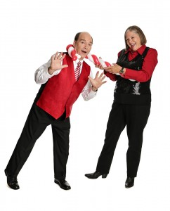 Caucasian woman in red shirt, black pants and vest uses red and white balloon candy cane to snag Caucasian man wearing white shirt, red vest, black slacks.