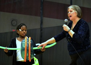 Marsha Gallagher entertains and instructs as she performs How to Catch a Mouse: Simple Machines at Work at an Odyssey of the Mind awards assembly.