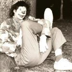 An old black and white image of Marsha Gallagher dressed as Modine the Clown leaning against a tree in the 1970s.