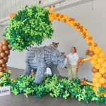 Caucasian woman stands beside a life size rhinoceros created from gray latex balloons. An arch built of balloons displays a giraffe and a tree. Green balloon foliage covers the floor. Qualatex balloons were used to create this scene.