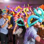 Young adults wearing colorful balloon hats crowd a dance floor with flowers, imaginary creatures of all kinds.