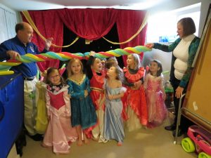 Girls dressed in princess costumes stand under multicolored balloon limbo stick.