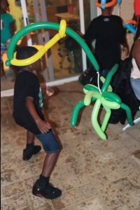 Green and yellow spider balloon hat adds to the fun at a birthday party